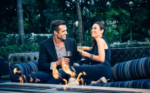 Couple drinking wine on black couch outdoors by fireplace