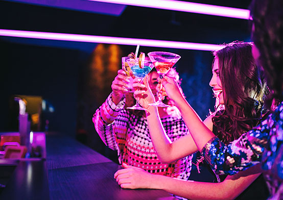 Two women having cocktails at club
