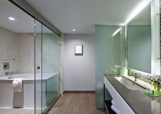 Bathroom with glass walls, long counter, tub & shower