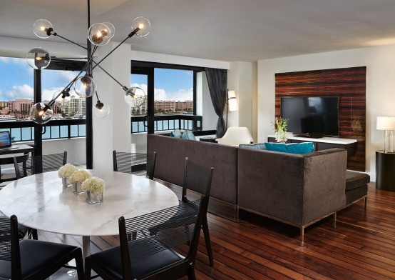 Presidential suite with kitchen table and hanging fixture, brown couch