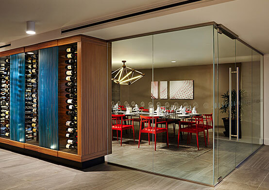 Stacked wine bottles next to glass wall of private dining room