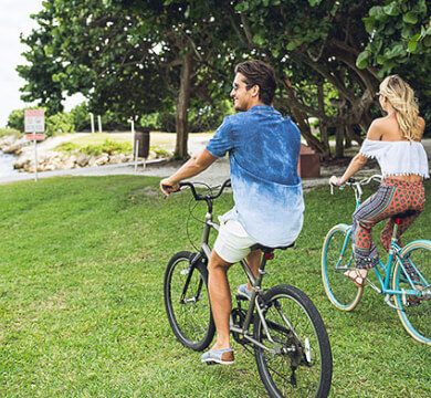 Couple riding bikes on grass