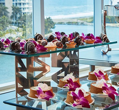 Wedding desserts served on glass tables with purple flowers