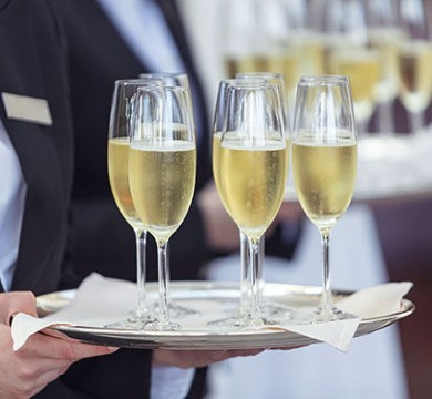 Waiter holding metal platter with champagne glasses