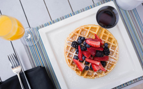 Waffles with berries and a glass of orange juice