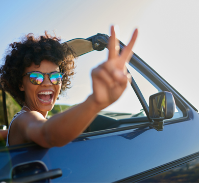 girl with sunglasses driving in convertible