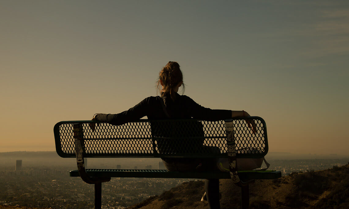 view from behind of a woman sitting on a bench overlooking the city at sunset