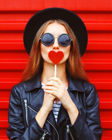 fashionable girl holding heart up to her lips wearing black hat