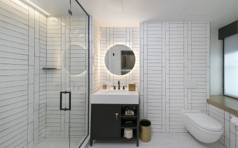 bathroom with white title, sink, and shower