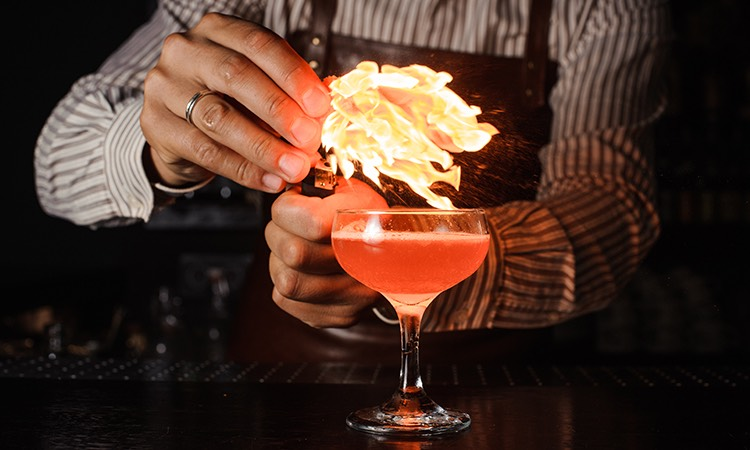 bartender putting a flaming garnish in a pink cocktail drink