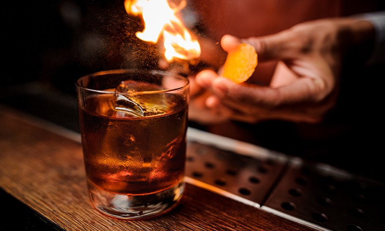 a bartender putting a flame to an orange twist as a garnish for a bourbon cocktail
