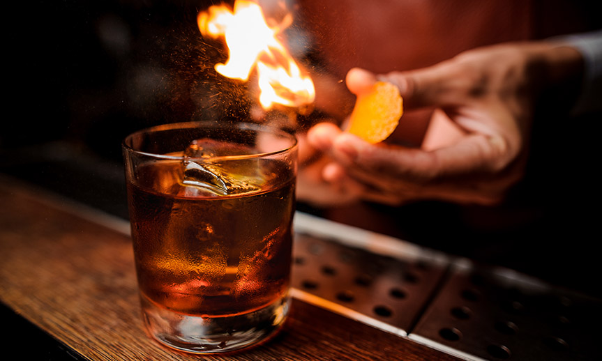 close up of a bartender lighting a lemon twist on fire to add as a garnish to a whiskey drink