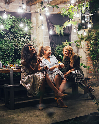 three women sitting at an outdoor dining table laughing and drinking together