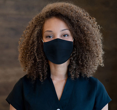 Woman with brown hair wearing face mask at front desk