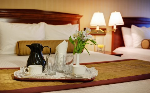 tray with coffee, flowers and mugs on top of hotel bed