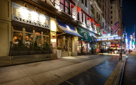 street light up at night with restaurants