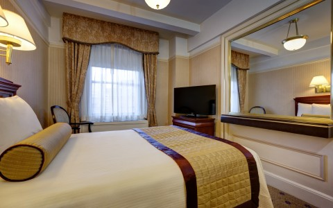 spacious hotel room with mirror and large window
