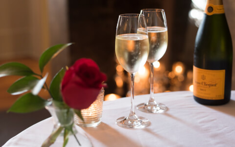 roses sitting on a table with a bottle of champagne and champagne flutes