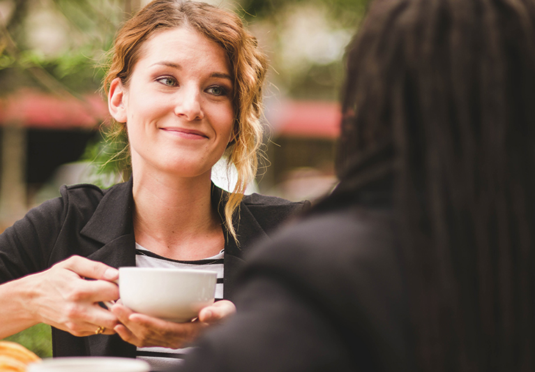 Woman holding cup of coffee next to other woman