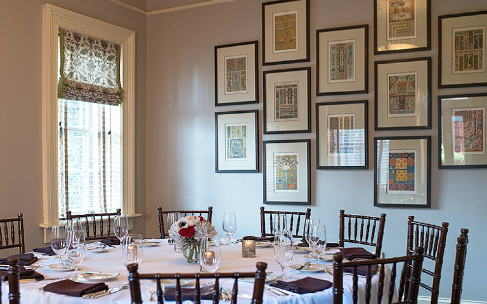 Circular table with wooden chairs set for meal with frames hung on wall