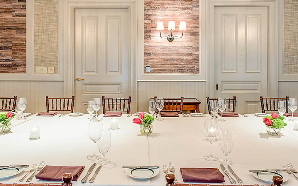 Long rectangular table set for meal with white doors & wooden walls in the back
