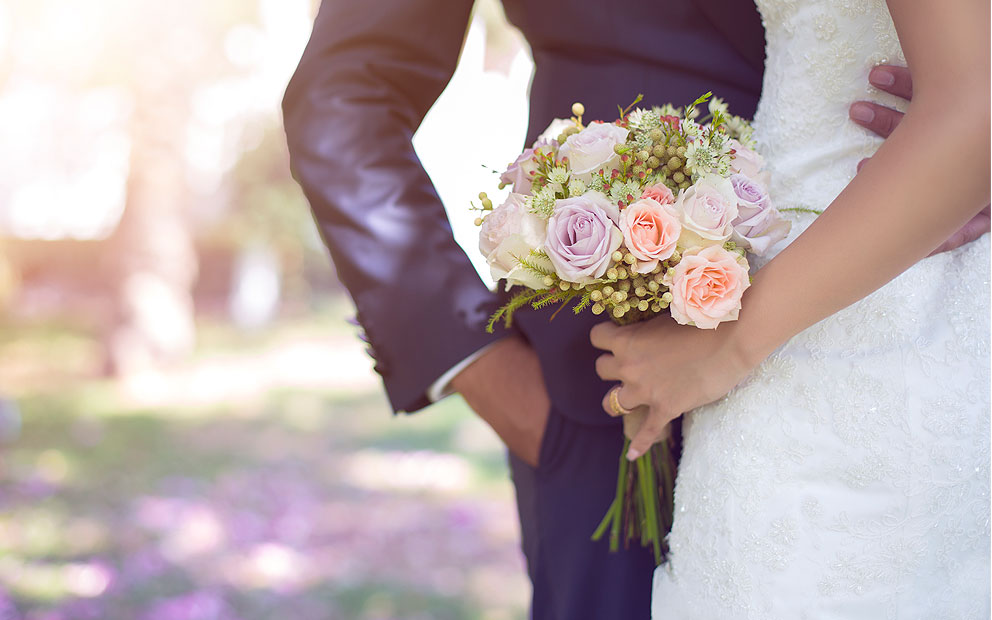 Bride holding flower bouquet next to groom