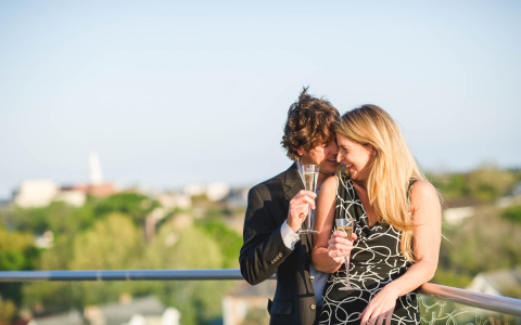 Couple laughing on rooftop with champagne glasses