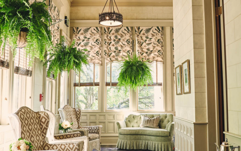 Sunroom with wicker padded chairs, long pattered rug & hanging ferns from ceiling