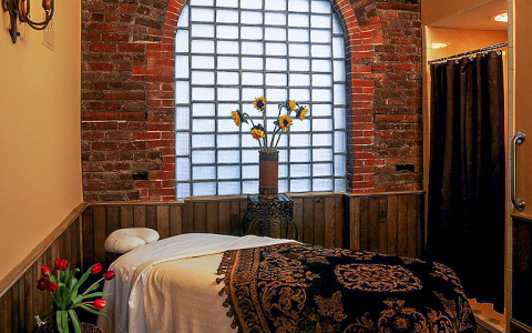 spa room with bed, brick walls & floral arrangements