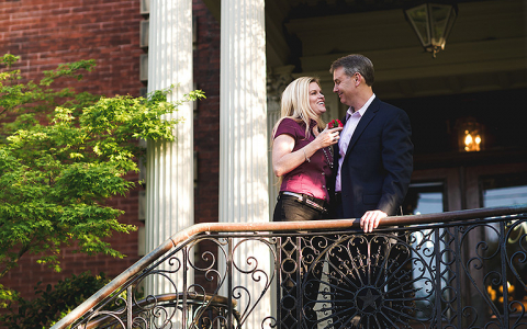 Couple standing close on balcony