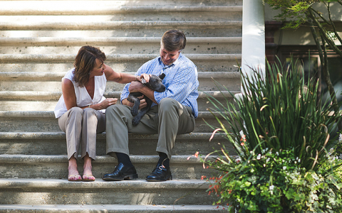 Couple sitting on stairs with dog