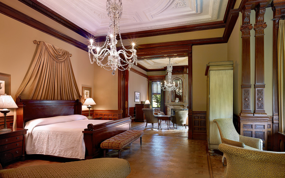 Room with king bed, chandelier & seating next to window