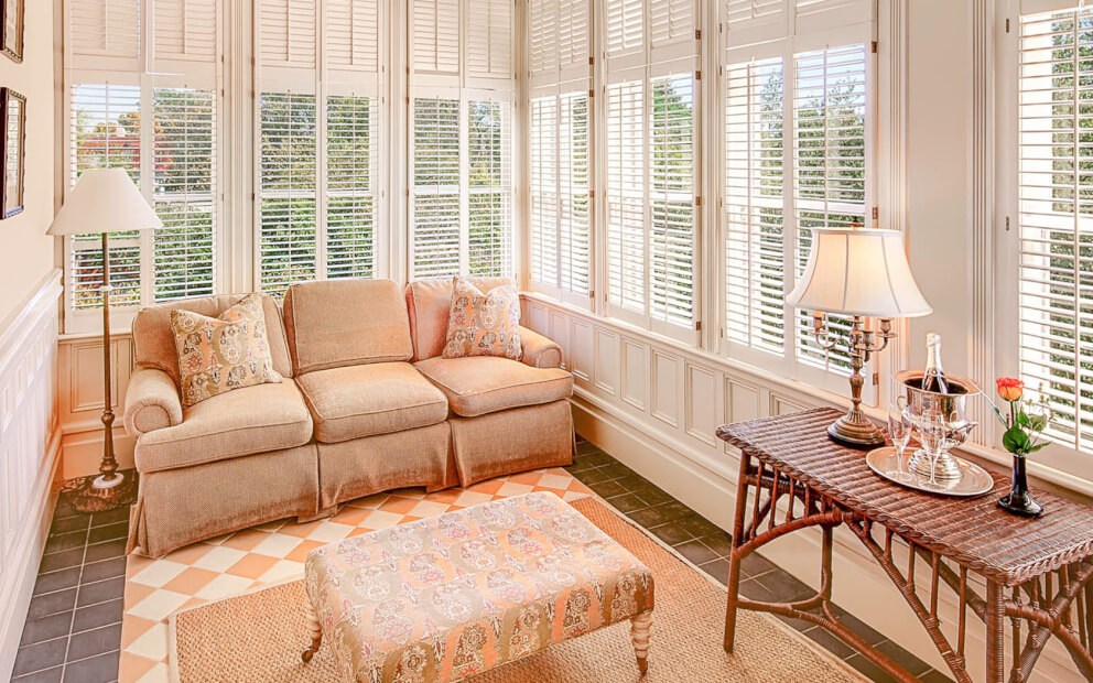 Sunroom with beige sofa, floral patterned table & throw pillows