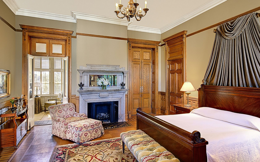 Room with king bed, wooden doors, grey curtains, decorative rug & fireplace