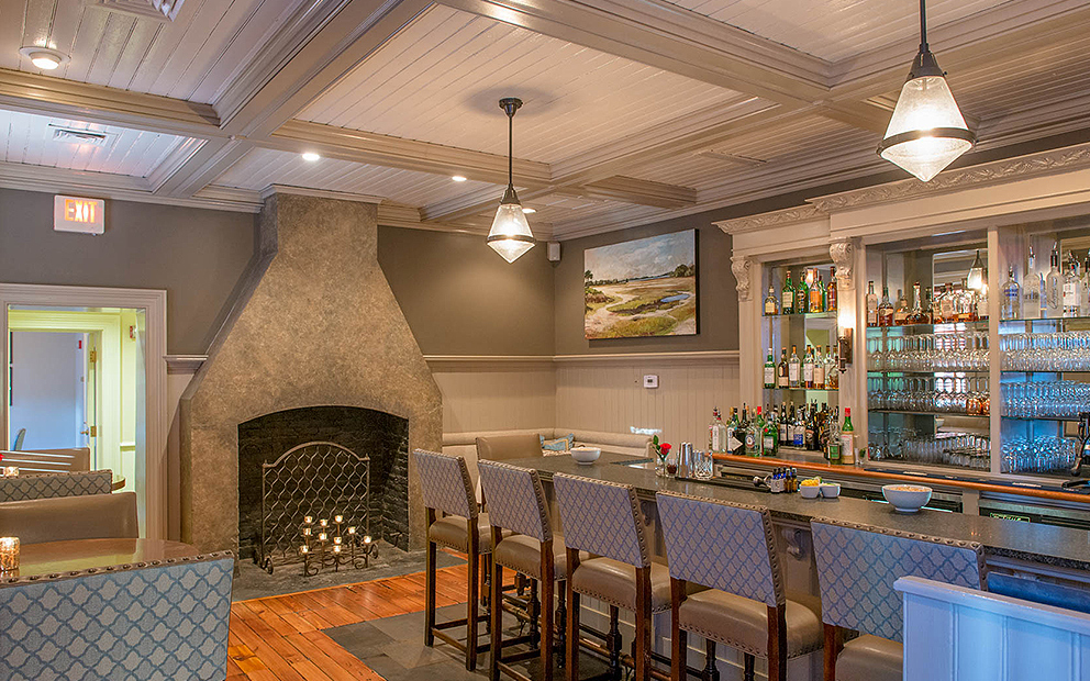 Dining space with fireplace next to blue stool bars in front of stocked bar with liquor bottles