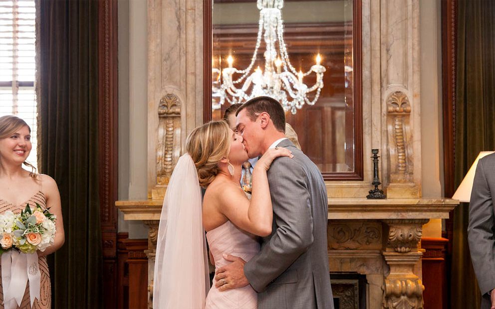 Wedding couple kissing next to fireplace