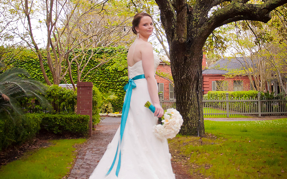 Bridesmaid with turquoise sash on dress standing in lawn