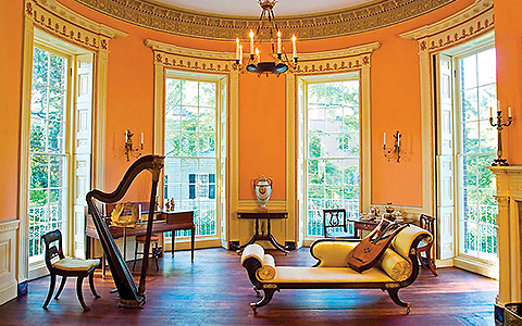 Antique styled room with orange walls, harp & piano