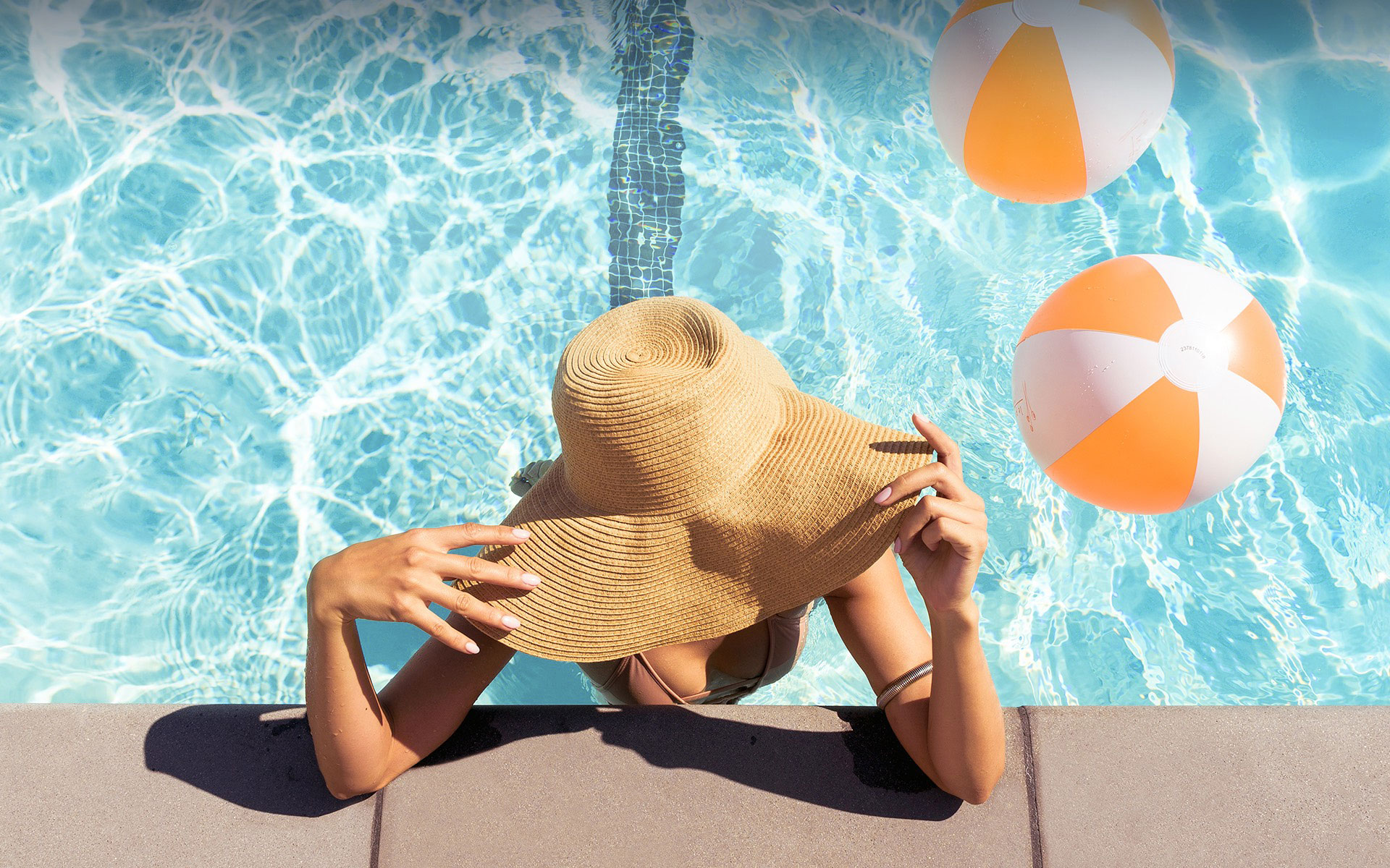 woman standing in the pool with her face covered by a wide brim hat