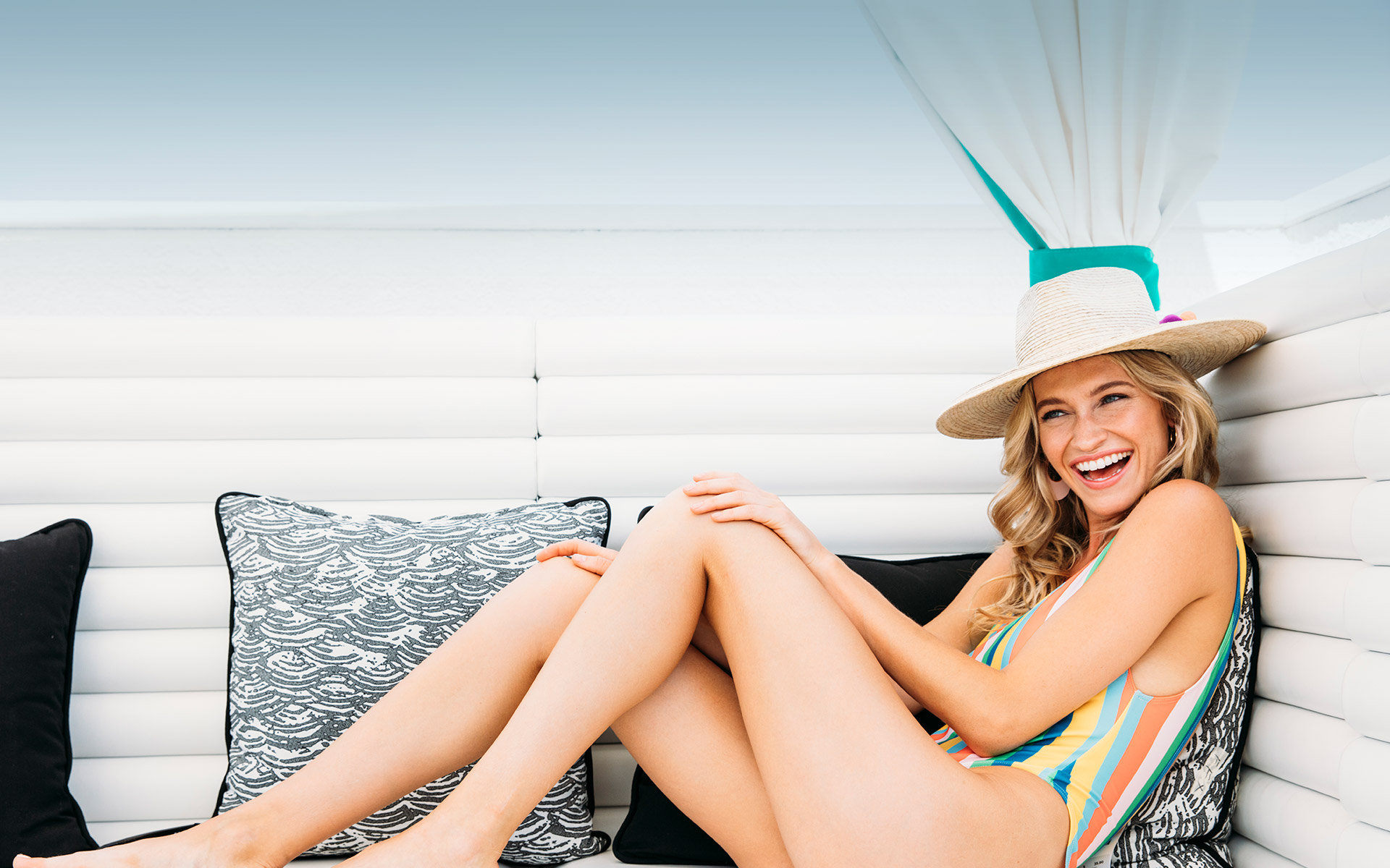 woman wearing a one piece swimsuit sitting on a cushioned bench outside