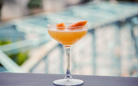 champagne flute with orange drink and garnish