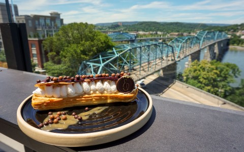flakey pastry on a plate outside and a large bridge in the back