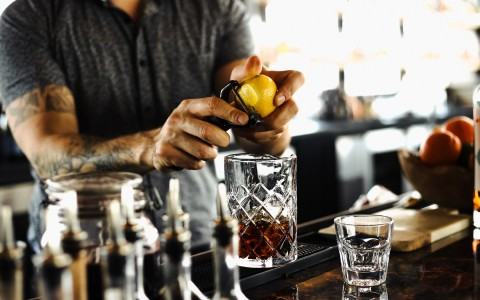 bartender peeling lemon zest onto glass