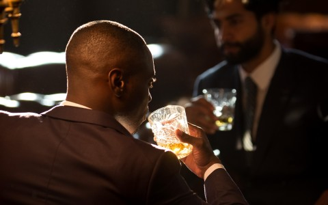 two men in suits having whiskey