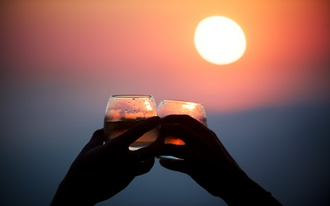 toasting while outside at sunset