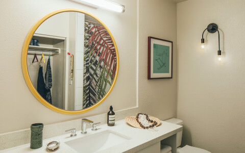 bathroom with a large circular mirror
