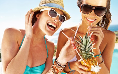 two women laughing with a pineapple drink