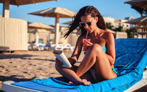 woman on the beach reading with a drink
