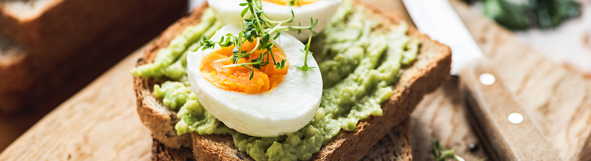 avocado on a piece of toast with a hardboiled egg on top garnished with fresh herbs