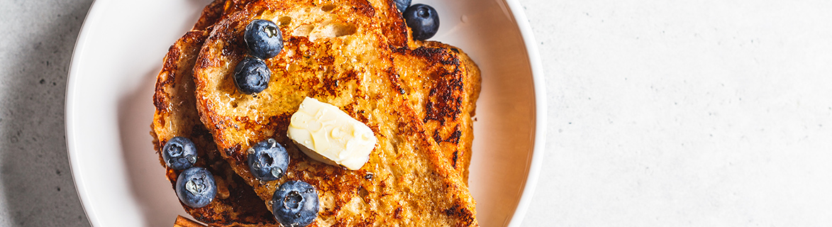 french toast on a white plate topped with blueberries and butter